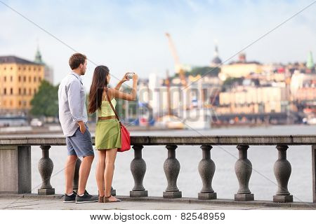 Europe travel tourist people taking pictures. Tourists couple in Stockholm taking smartphone photos having fun enjoying skyline view and river by Stockholm's City Hall, Sweden.