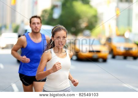 City runners - urban new yorkers people running in busy street in New York NYC. Young adults asian caucasian jogging in traffic on Manhattan during summer.
