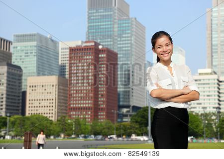 Businesswoman in Tokyo city skyline, Japan. Beautiful young casual professional woman standing portrait for Japanese business concept in Japan. poster