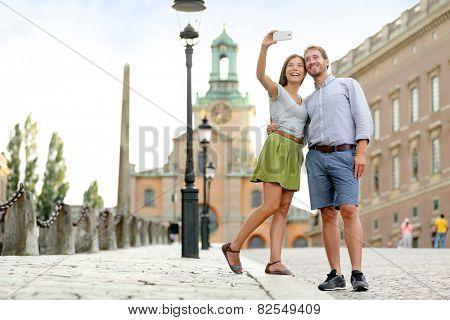 Selfie couple taking pictures at Stockholm cathedral and royal palace in Gamla Stan (Old Town) in the capital of Sweden. Tourists people taking travel photos with smartphone on summer holidays. poster