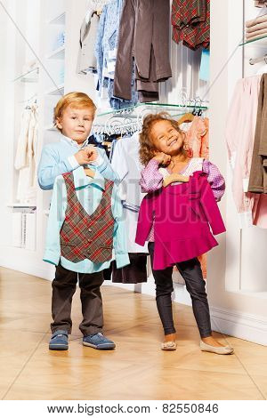 Boy fits vest and girl with sweater in store