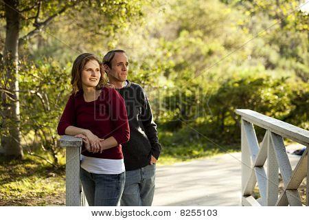 Couple pondering on wooden bridge