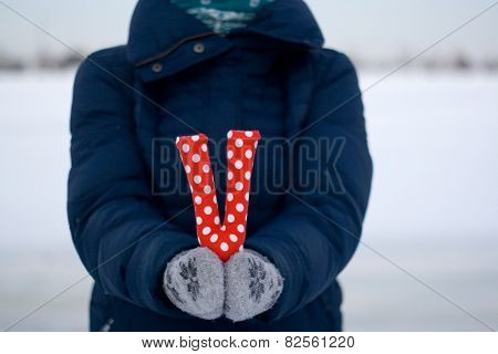 Girl In Blue Down Jacket And Gloves Holding A Letter Of Fabric