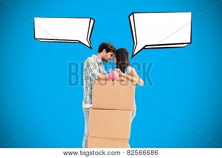Happy young couple with moving boxes and piggy bank against blue background with vignette