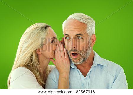 Woman whispering a secret to husband against green vignette