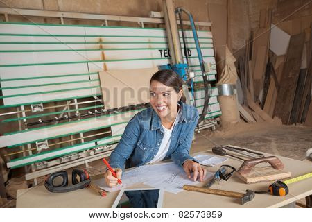 Happy female carpenter working on blueprint while looking away in workshop