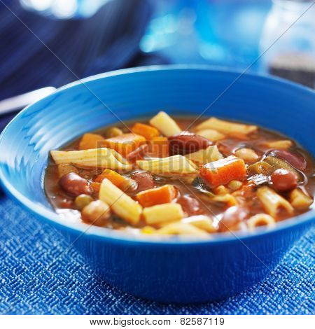 minestrone soup in blue bowl close up