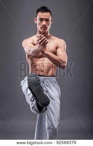 Young asian man workout over grey background karate kick