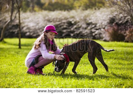 Child with a boxer dog at the city park