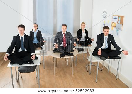 Meditating Businesspeople Sitting On Desk