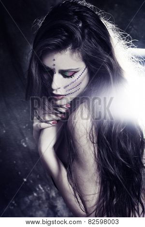 beautiful young fairy like woman with long hair and fantasy make up and purple zircons on face, studio shot