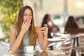 Tired woman yawning while is working on the phone at breakfast in a restaurant poster