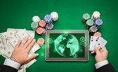 casino, online gambling, technology and people concept - close up of poker player holding playing cards, chips and earth projection with users icons on tablet pc computer screen at green casino table poster