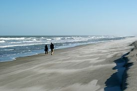 People Walking Along The Beach.