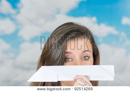 brunette holding a paperplane in front of cloud themed background