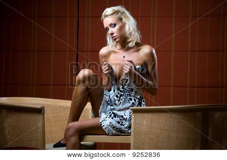Sensual young woman sitting on a table