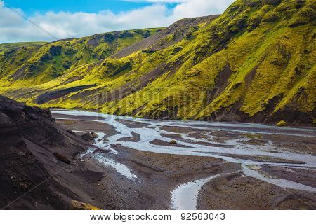 Canyon Pakgil in Iceland. Picturesque basalt hills covered with green grass and moss-polar. Streams from melting glaciers flowing down the canyon