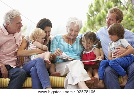Multi Generation Family Reading Book On Garden Seat