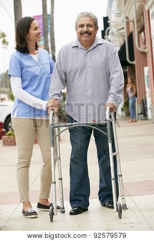 Carer Helping Senior Man To Use Walking Frame