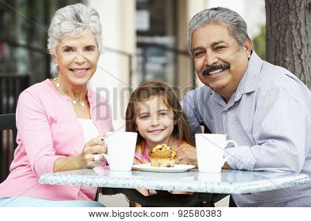Grandparents With Granddaughter Enjoying Snack At Outdoor Caf\x81_