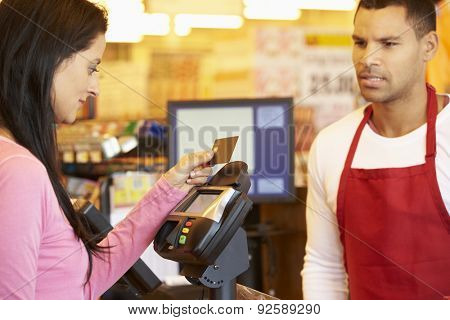 Customer Paying For Shopping At Checkout With Card