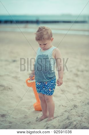 Little boy child standing with a wet shirt on the beach