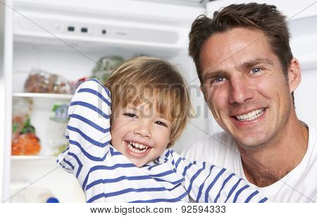 Father And Son Getting Snack From The Fridge