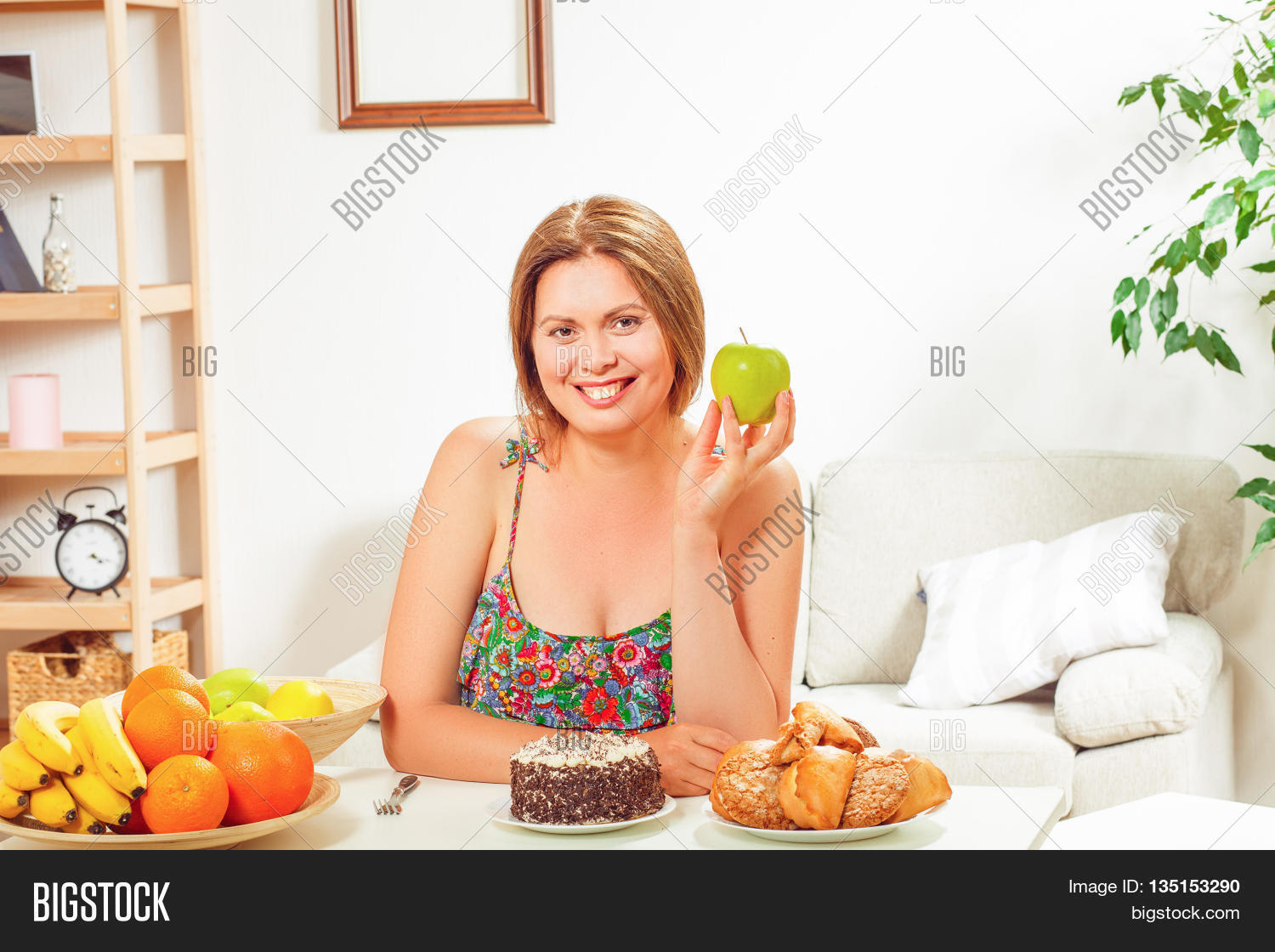 Portrait of toothy smiling fat woman sitting at table and holding green apple in front of her at home. Diet concept.