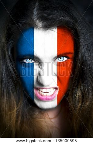 Portrait of a woman with the flag of the France painted on her face.