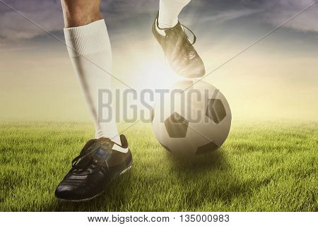 Foot of soccer player using a ball for training kick a ball shot at the field at sunrise time