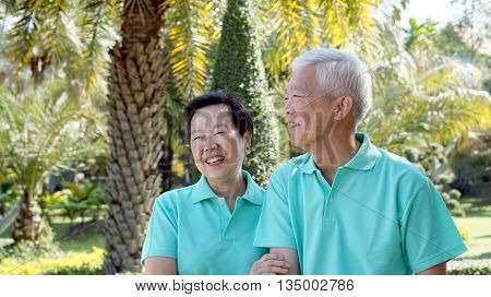 Asian Senior Couple Smiling Togher In Green Nature Background