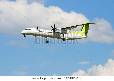 SAINT PETERSBURG, RUSSIA - MAY 17, 2016: Aircraft Bombardier DHC-8-402 NG (YL-BAQ) airline airBaltic in the cloudy sky