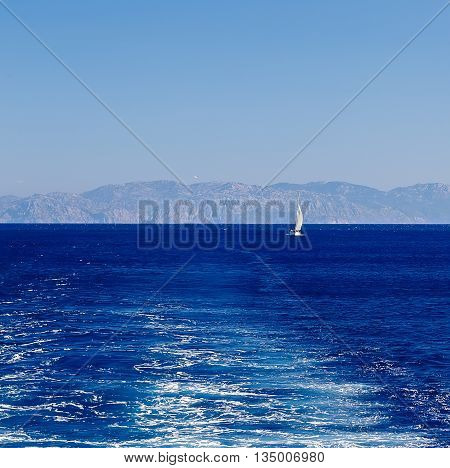 sailing yacht at sea on the background of mountains and the track of ship engine