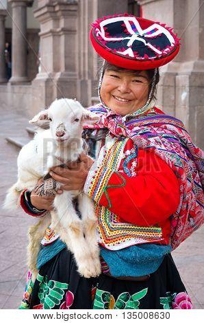 CUSZO PERU - MARCH 18 2015: Peruvian woman in traditional dresses pose for tourists in Cuzco Peru