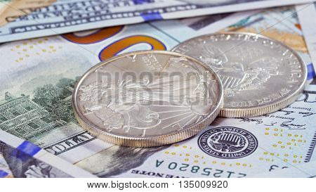 Silver American eagle coins over 100 dollar bank notes background