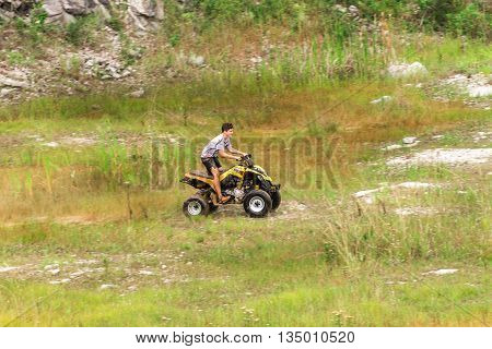 Off Road On Quad Bike Rally Over Mud Puddle