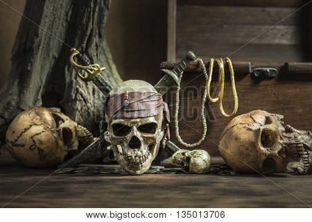 pirate skull with two swords and treasure coffer over three head of human background still life style pirate concept for halloween