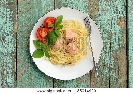 Spaghetti with basil tomatoes and salmon on turquoise shabby table overhead view
