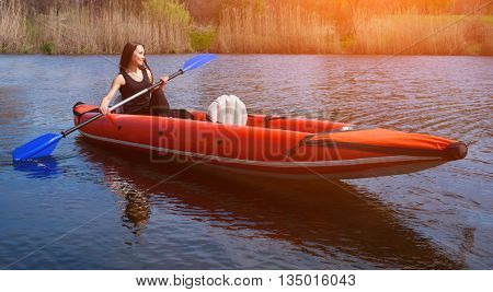 The smiling girl -the sportswoman with longdark hair in blacksportswear rows with an oar on the lake in a red inflatable canoe in a warmsummersunny day. Occupation by sports rowing on a kayaking.