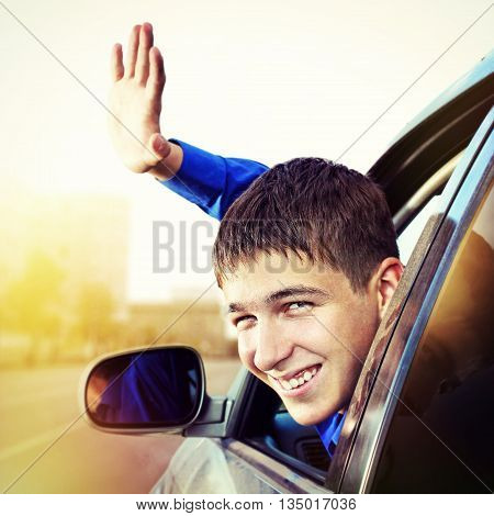 Toned Photo of Cheerful Young Man sit in the Car on the City Street