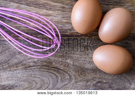 eggs and pink beater on wooden table