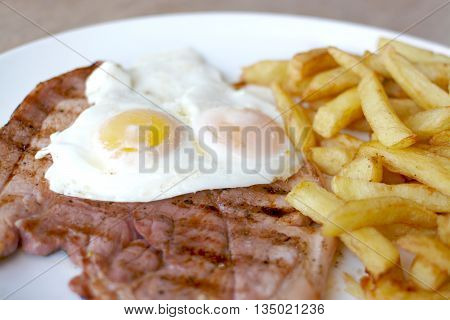 Close up view of gammon, fried eggs and golden chips