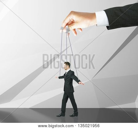 Hand manipulating businessman puppet on ropes. Abstract concrete wall background. Concept of control