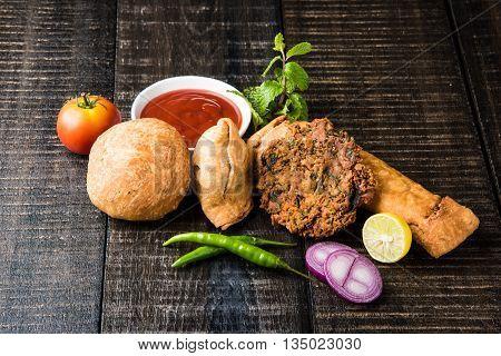 coriander vada or kothimbir vada, samosa, kachori, daal vada on brown wooden planks. indian assorted snacks. Indian snacks combination. Indian snacks group