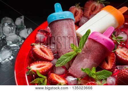 Strawberry ice cream sundae popsicles on red plate with ice cubes chopped strawberries and mint leaves on a black background. Strawberry ice cream sundae popsicles. Horizontal.
