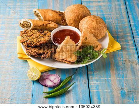 coriander vada or kothimbir vada, samosa, kachori, daal vada on brown wooden planks. indian assorted snacks. Indian snacks combination. Indian snacks group, indian favourite snacks, asian spicy snacks