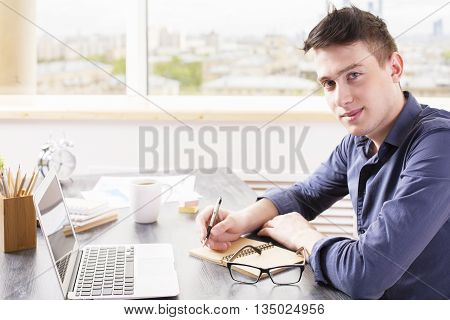 Education concept with young man writing in notepad on desktop with laptop coffee cup glasses and other items