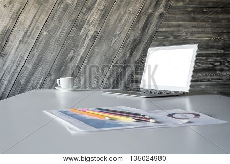 Side view of office desktop with blank white laptop coffee cup business report and colorful pencils on wooden background. Mock up