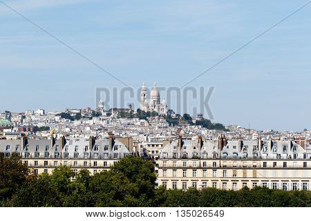Basilica of the Sacre Coeur on Montmartre, Paris, France with the capital cityscape in the foreground. Horizontal with copy space for text