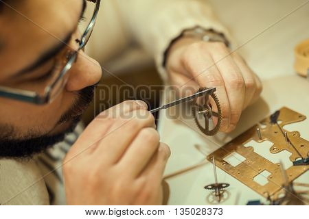 A watchmaker or repair man in action viewing very closely a swiss watch.